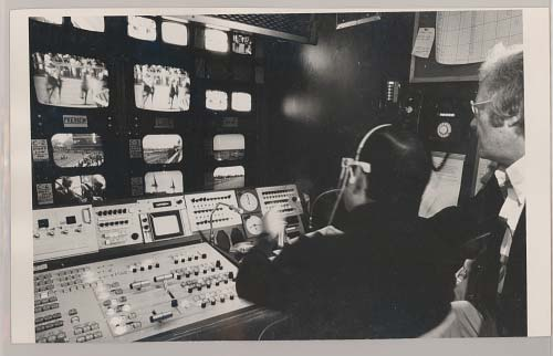 Two men sitting in front of television broadcasting controls