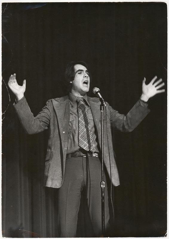 Man gesturing behind a microphone