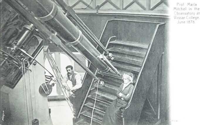 "A black and white post card featuring an older woman, Maria Mitchell sits on steps in front of a telescope. The text on the postcard reads ""Prof. Maria Mitchell in the Observatory at Vassar College. June 1878."""