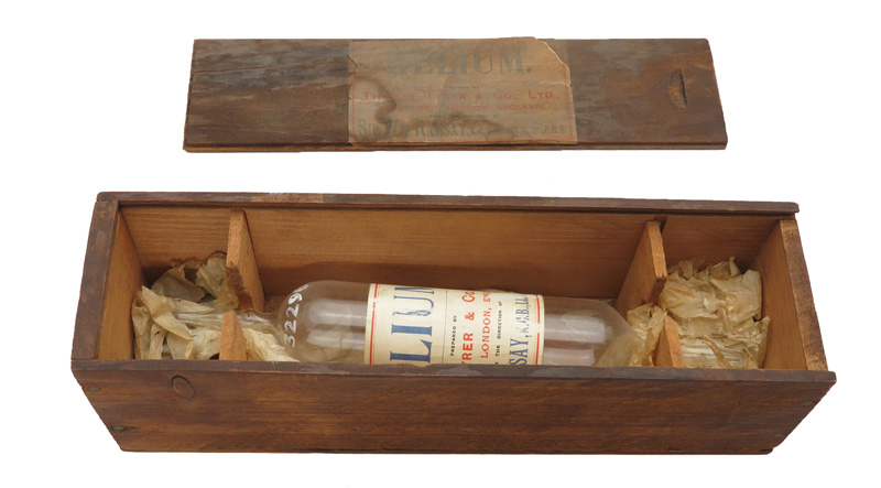 """Glass tube labeled helium inside a long, wooden box, adjacent to the box's removed cover, which also reads """"Helium"""""""