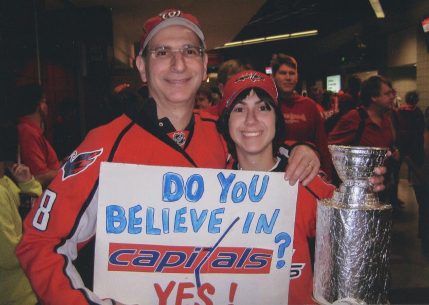 Two hockey fans posing with a sign and a foil trophy cup