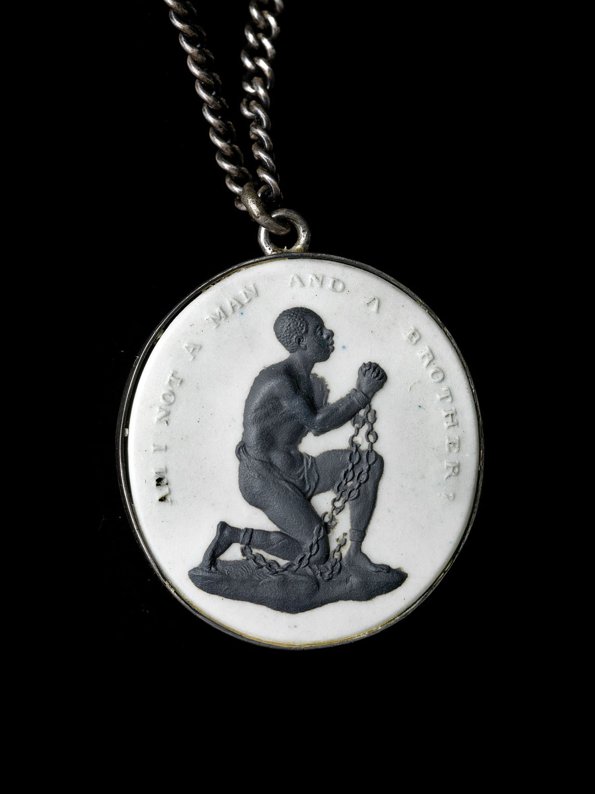"A white medallion with a raised image of a man kneeling in chains. Above him is the text ""Am I not a man and a brother."""