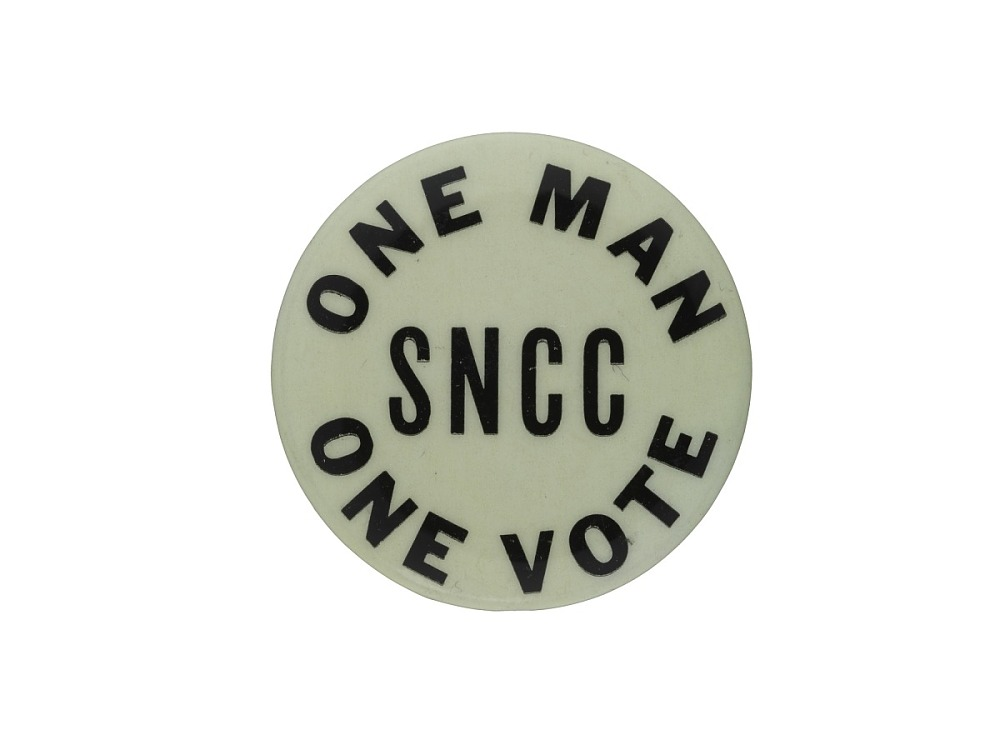 "A black and white pin that reads ""One Man, One Vote."""