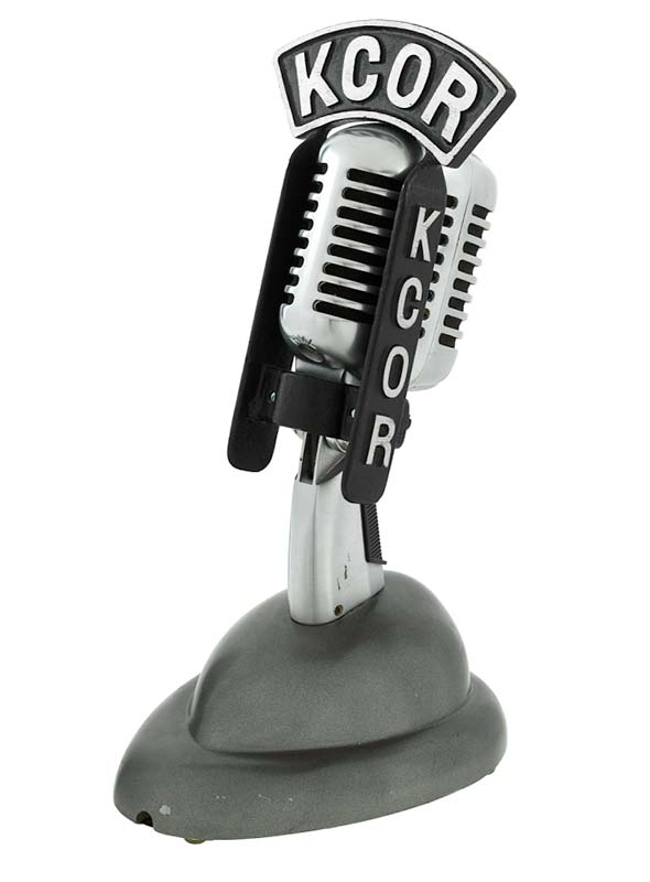 Metal microphone on stand with the letters KCOR