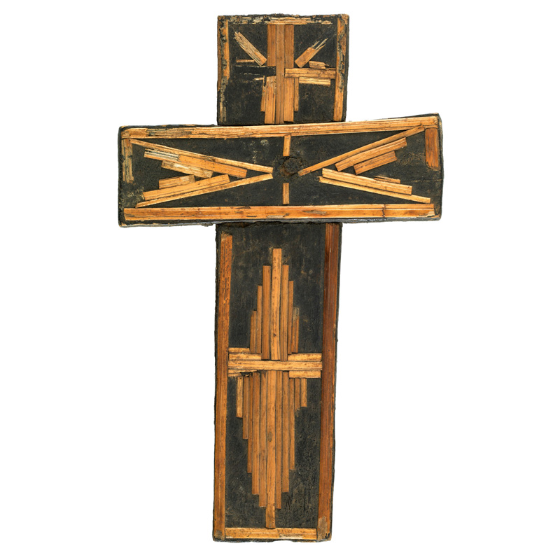 Wooden cross decorated with straw arranged in geometric patterns