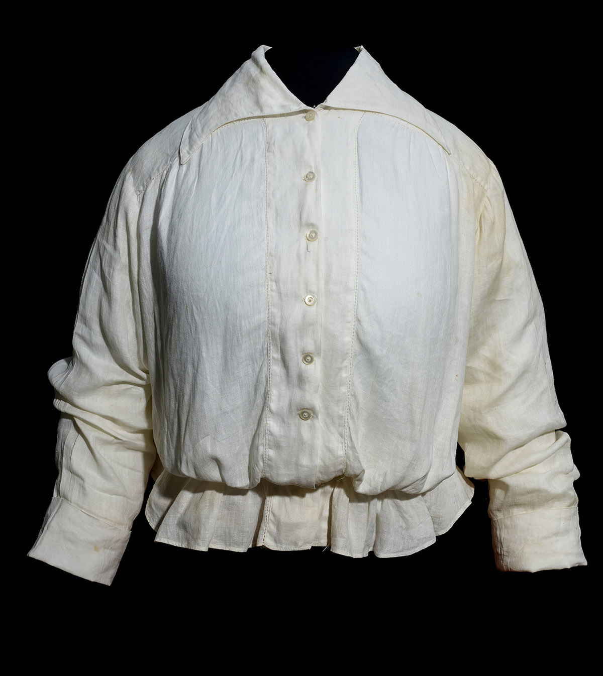 A white shirt that appears to be cotton or linen. It has long sleeves, buttons up the front. There's a large color that would drape over the wearer's shoulders. It gathers around the waist and the hem flairs out in a bit of skirt.