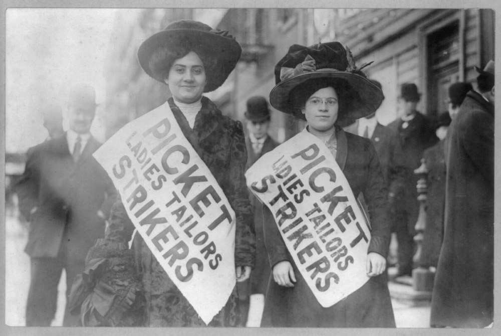 "A grey-scale photograph. In focus, in the center of the frame, are two women wearing sashes that read ""Picket Ladies Tailors Strikers."" The women look respectable--wearing fine coats and larger hats. Men in bowler caps stand in the background."