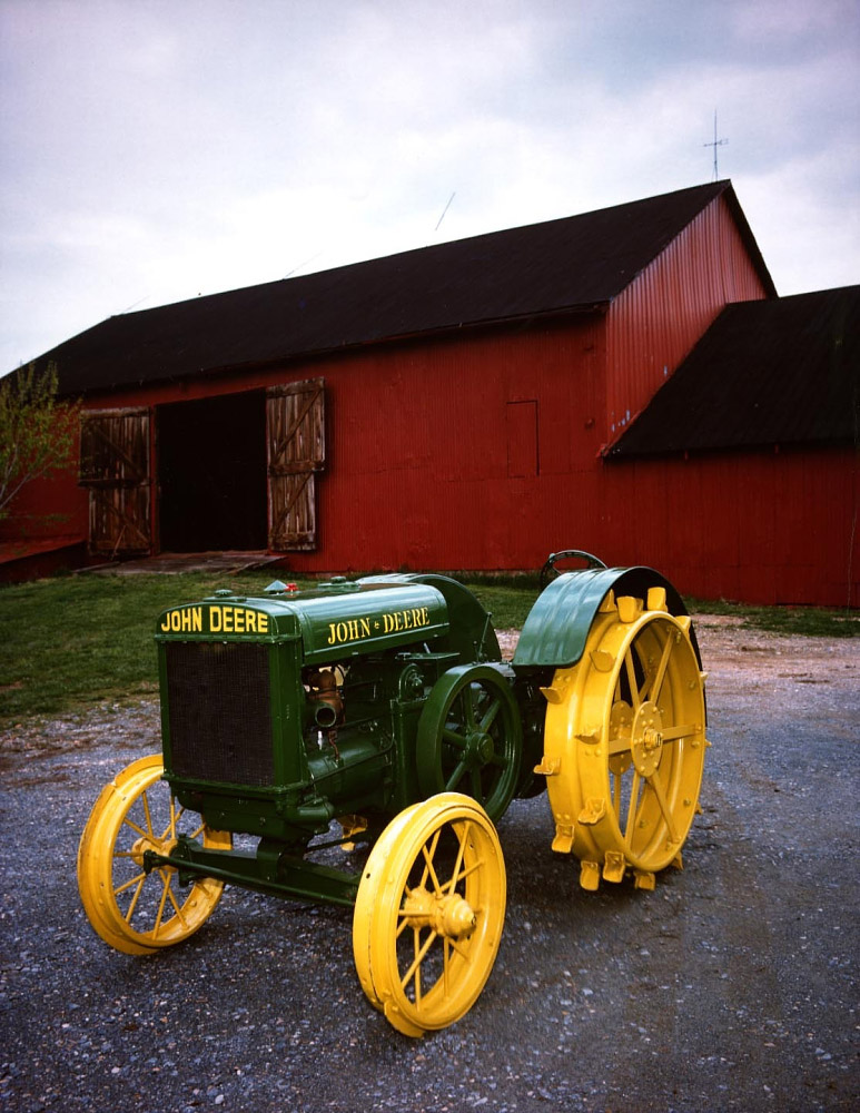 A green John Deere tractor in front of a red barn.