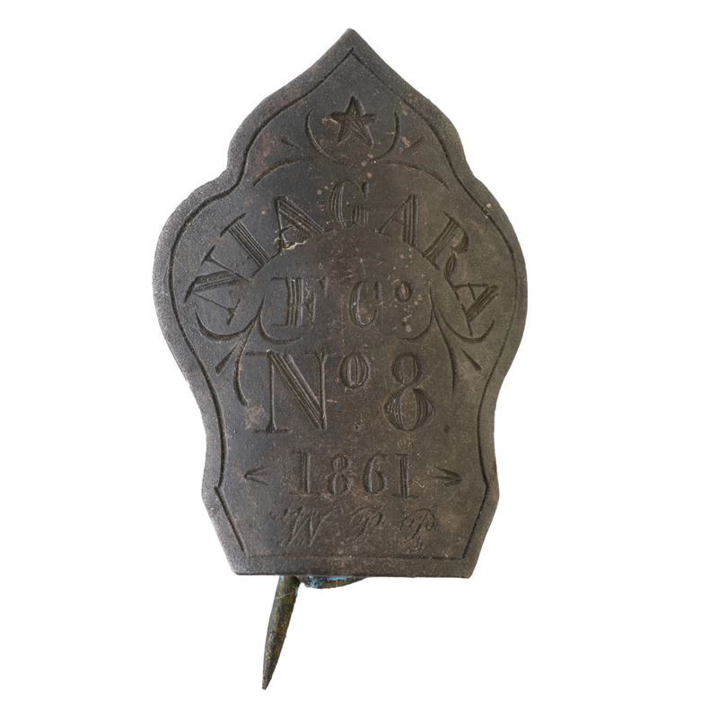 """Small metal badge, decorated with an engraved star and other small line flourishes. The main engraving reads """"Niagra, F. C., No. 8, 1861, W. P. P."""""""