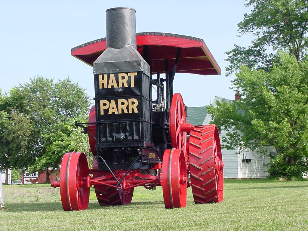 The Hart Parr tractor sits in a field. Like the Frick tractor model, it has a black body with a steam chimney on the front, a red awning over the works, and red wheels.