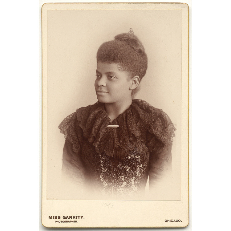 A black and white photograph of Ida Bell Wells-Barnett, a black woman in her 30's, facing towards the left. She is wearing a black dress and her hair is in a bun.