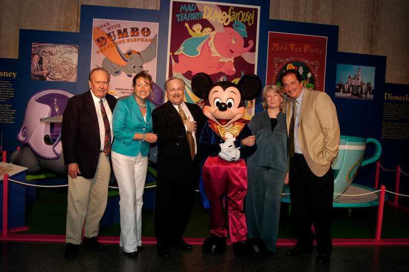 Party attendees pose with Mickey Mouse