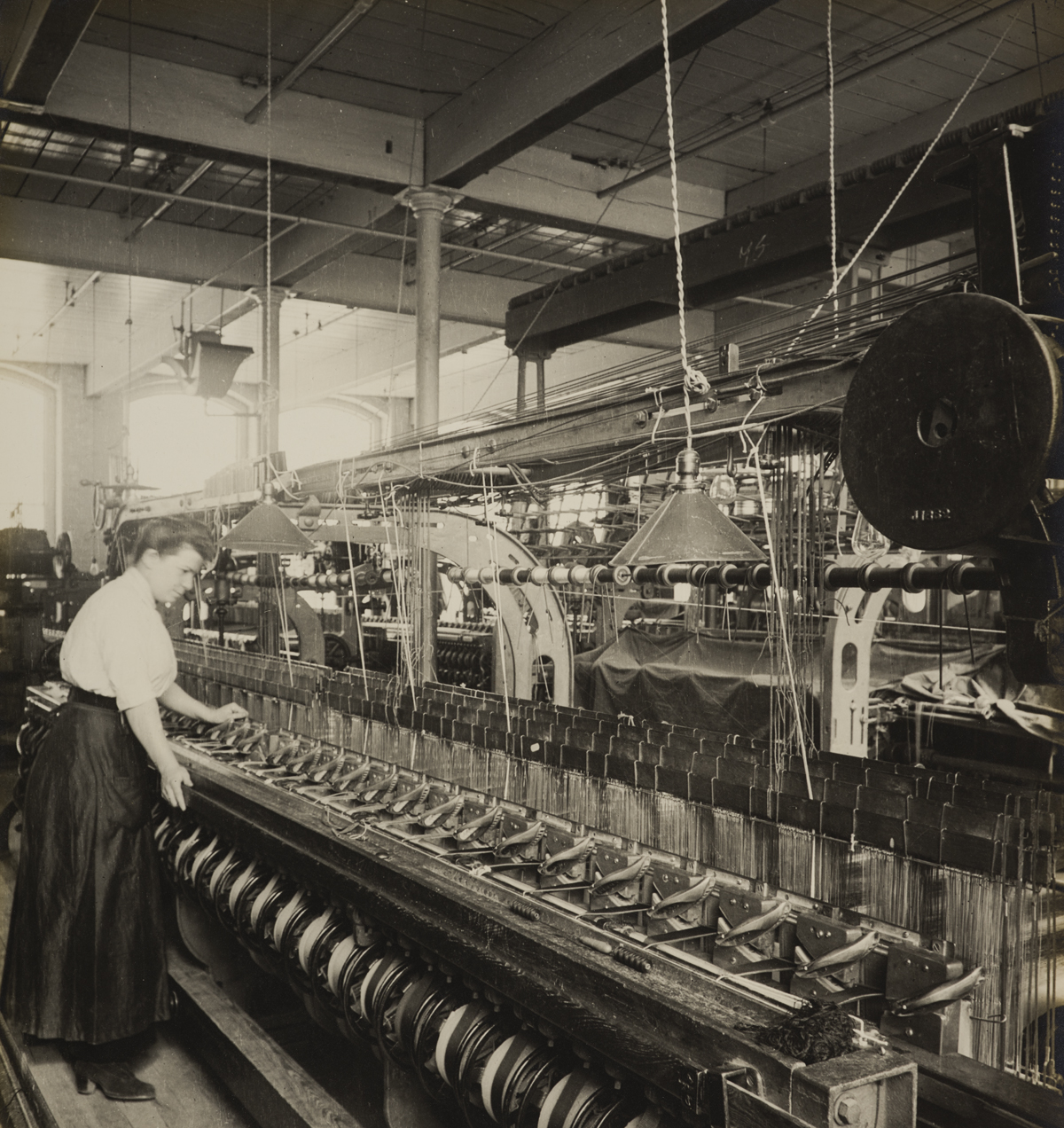 A worker at the loom in Cheney Brother silk factory.