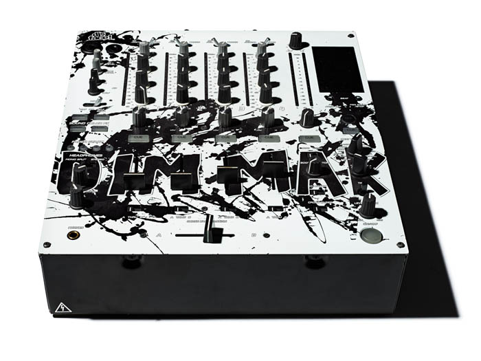 A piece of white DJ equipment with lots of levers and switches