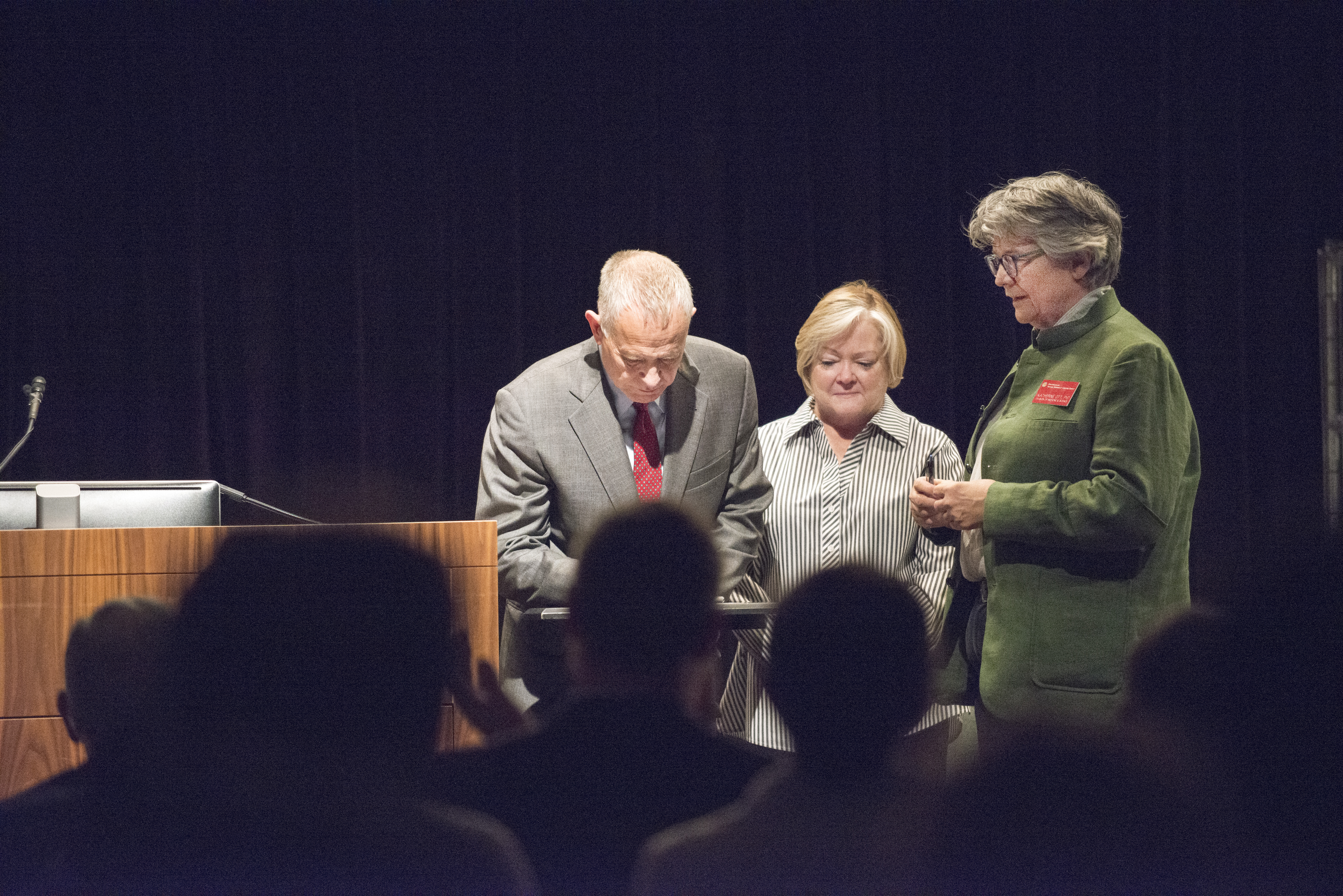Three people on a stage, one man and two women. Solemn expressions. The man signs a document while the women look on. Black curtain behind them.