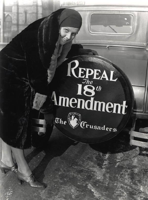 "A hub cap cover with the text ""Repeal the 18th Amendment"" and a woman standing by it."