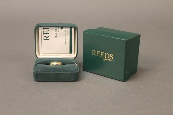 A men's wedding ring in a green Reed's box