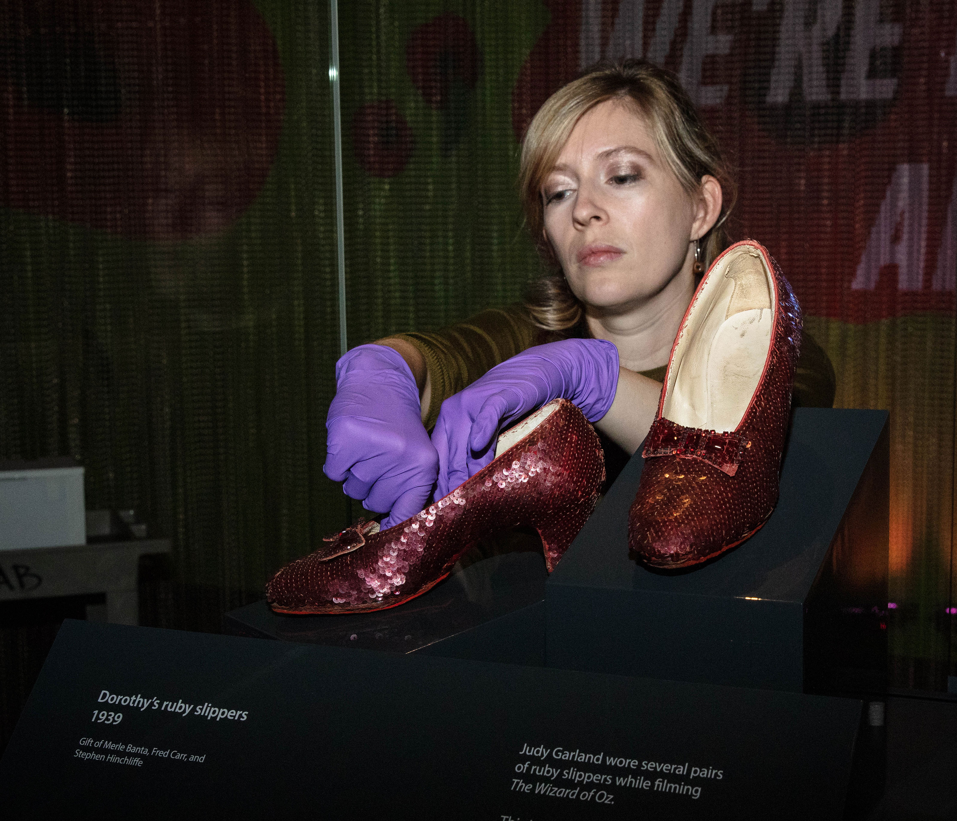 f134eef2c2c4 Woman wearing purple latex gloves presses gently into the inside of one of  the Ruby Slippers
