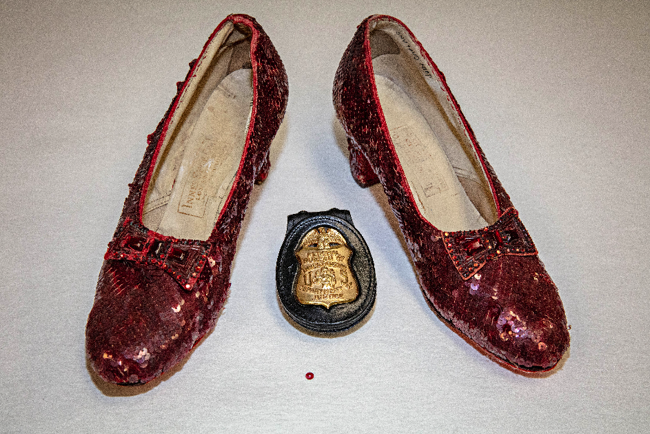 Two red shoes, kitten heels, covered in red sequins. In the center, a single red sequin. And an FBI badge.