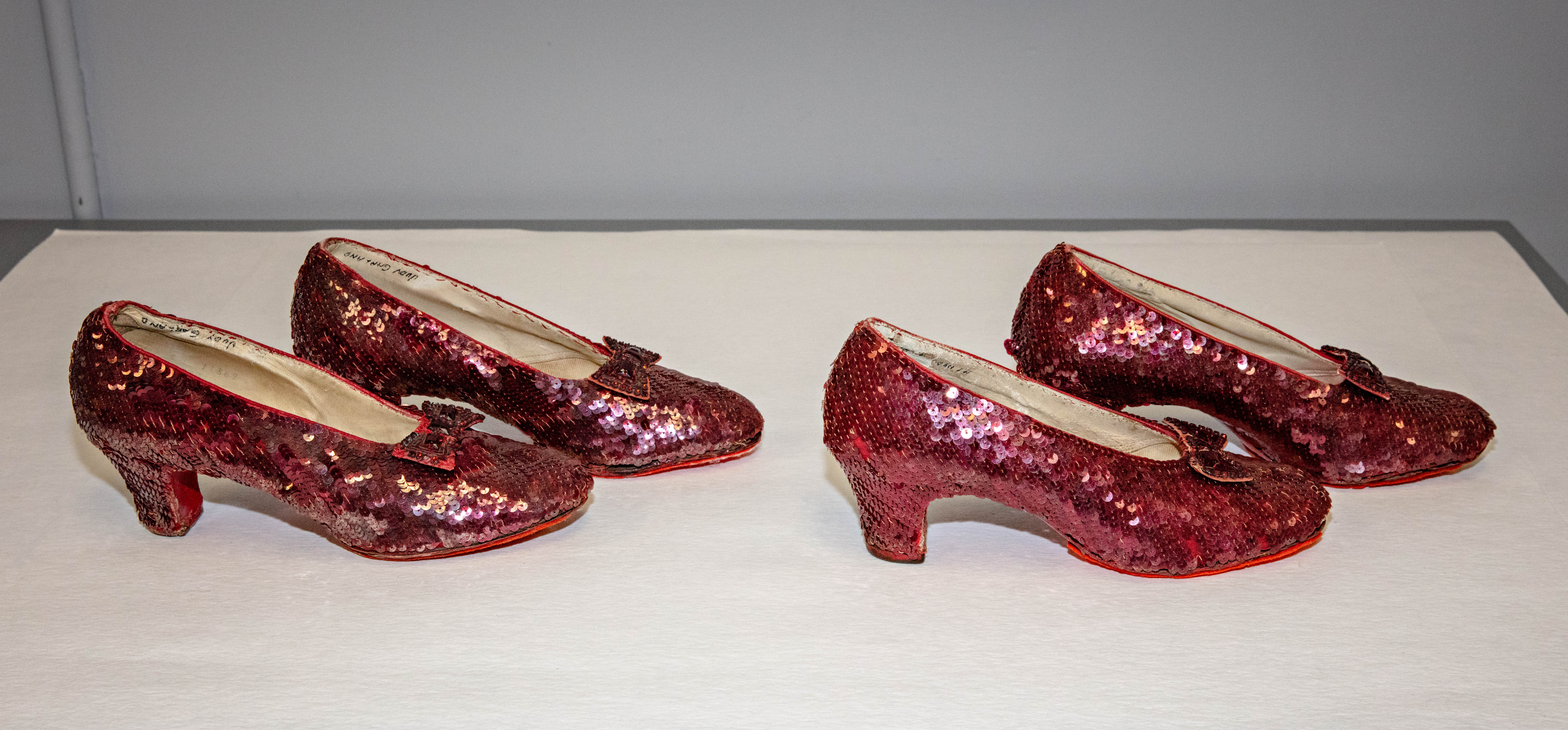 Two pairs of red shoes covered in red sequins.