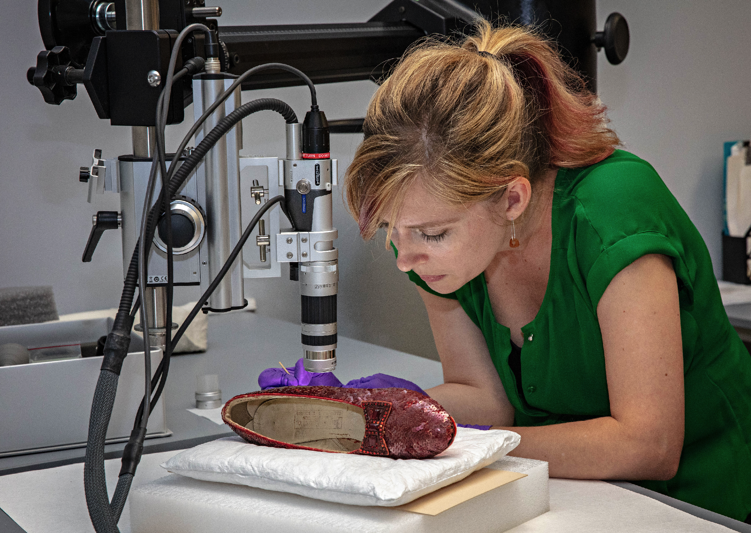 A woman wearing a green shirt looks at a sequin-covered red shoe, using a stick-like instrument to examine in. Beside her, a microscope.