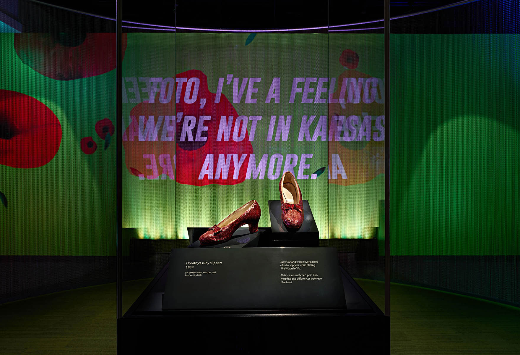 "In a display case, the Ruby Slippers, kitten heels covered in red sequins with a bow. Behind them, ""We're not in Kansas anymore"" quote in white, all-caps, bold typeface on a mural that is green with big, red poppies."