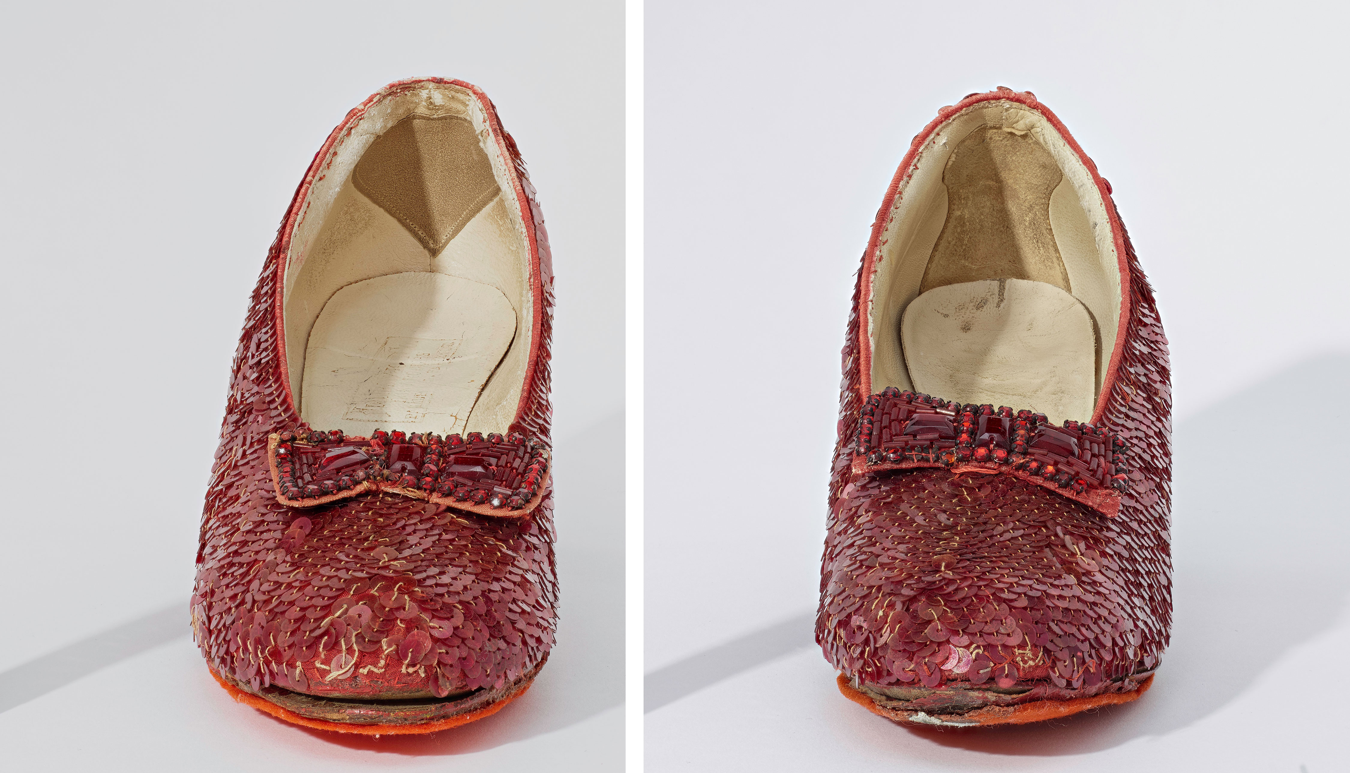 Two red shoes covered in sequins with bows. Inside each shoe, you can see the hell. They have different details in the heel. One is a tear. The other is an hour glass shape.