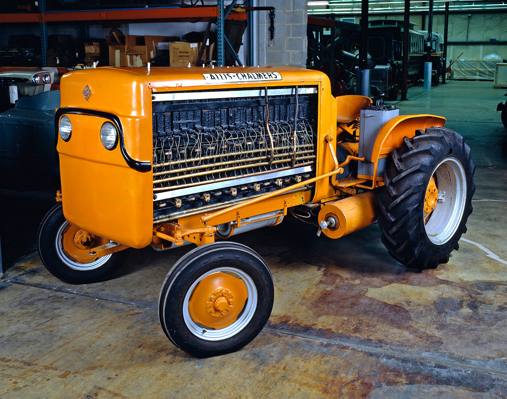 A yellow tractor, with a large front part with many wires.