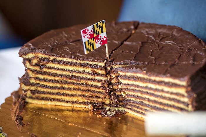 A multiple layer cake with a Maryland flag at the top.