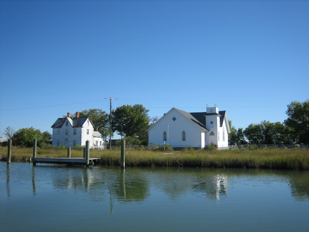 Calm, sunny day. White houses on the water.
