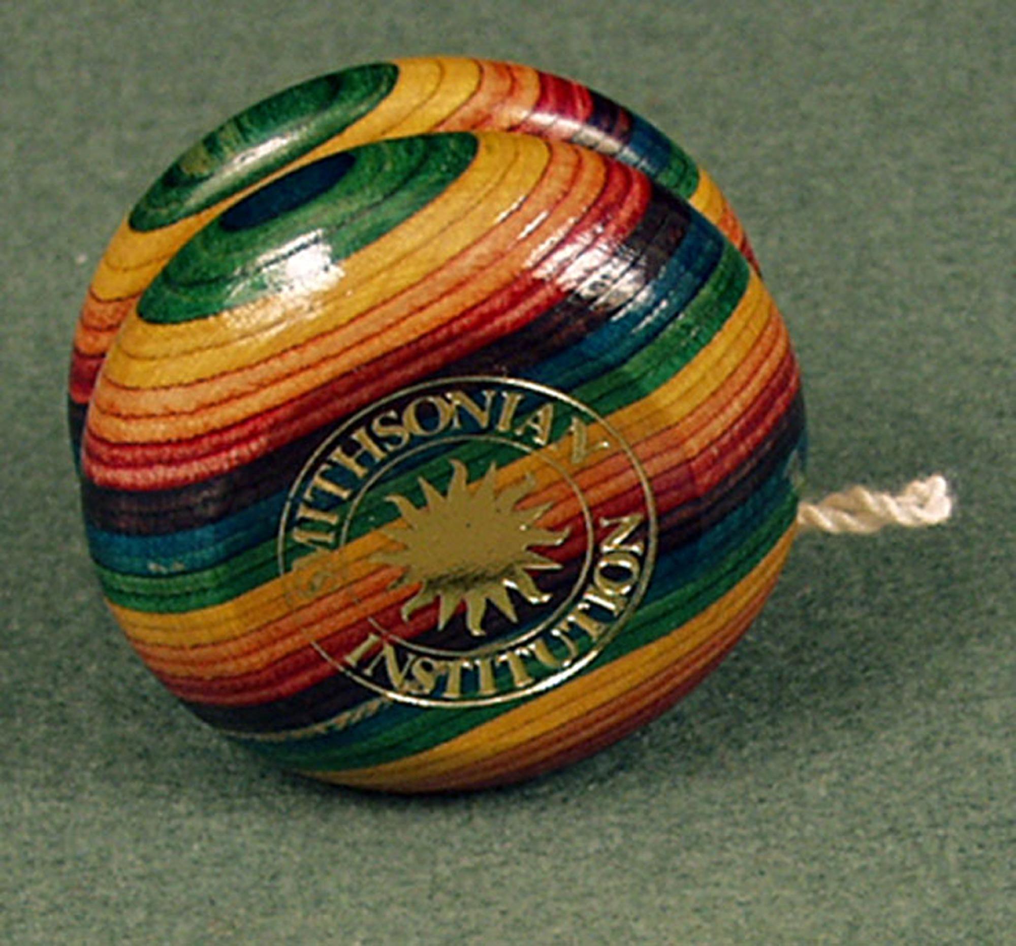 Wooden yo-yo with rainbow stripes and a golden Smithsonian logo