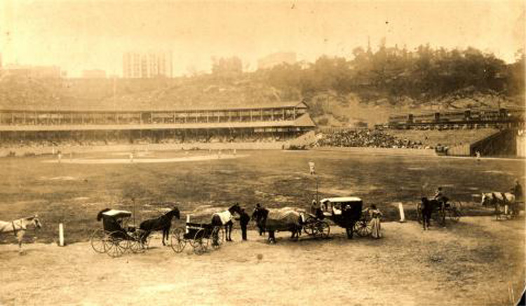 A baseball game on the polo grounds with horses and carriages in the foreground