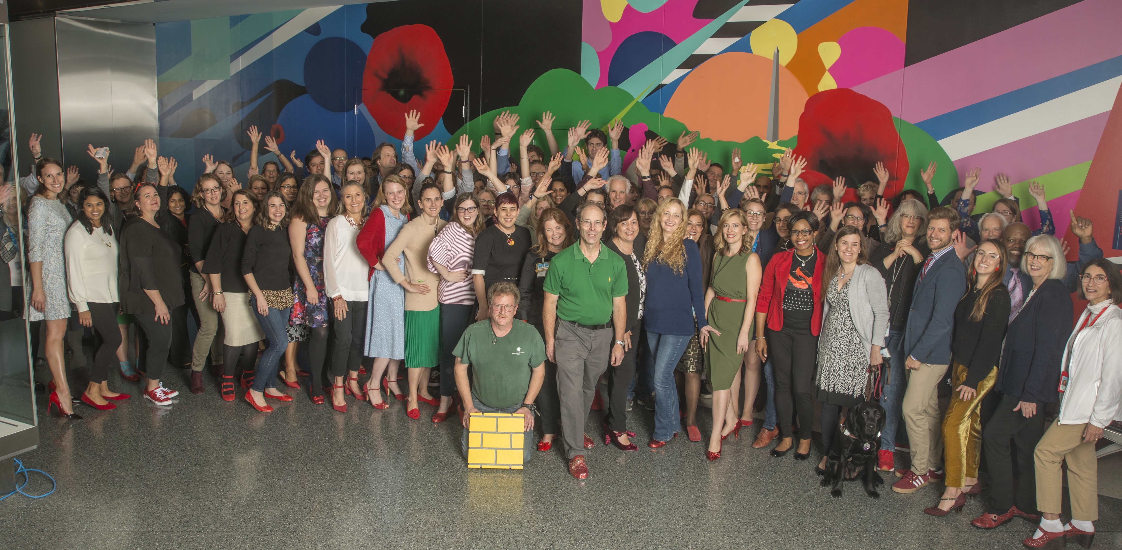 Group photo in front of a colorful mural. Many smiling staff members, most of them wearing red shoes. One in front has a section of prop yellow brick road.