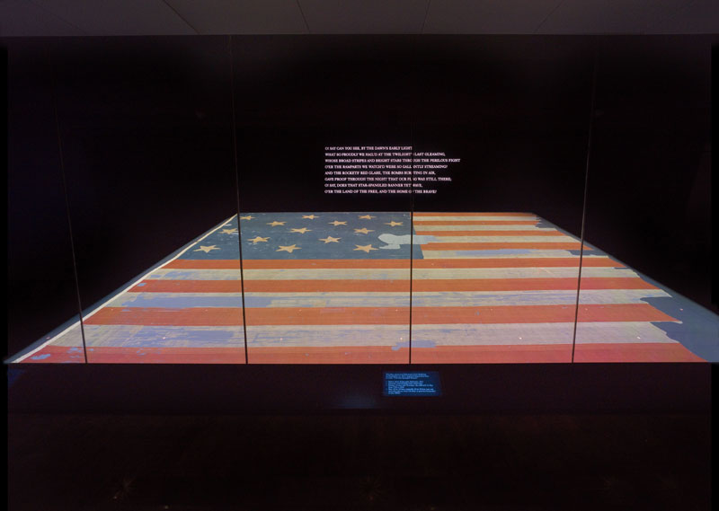 Star-Spangled Banner flag on a horizontal table in dark room with first stanza of national anthem in white lights behind it on the wall