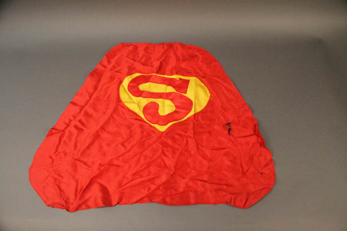 A small red cape with a yellow S on it.