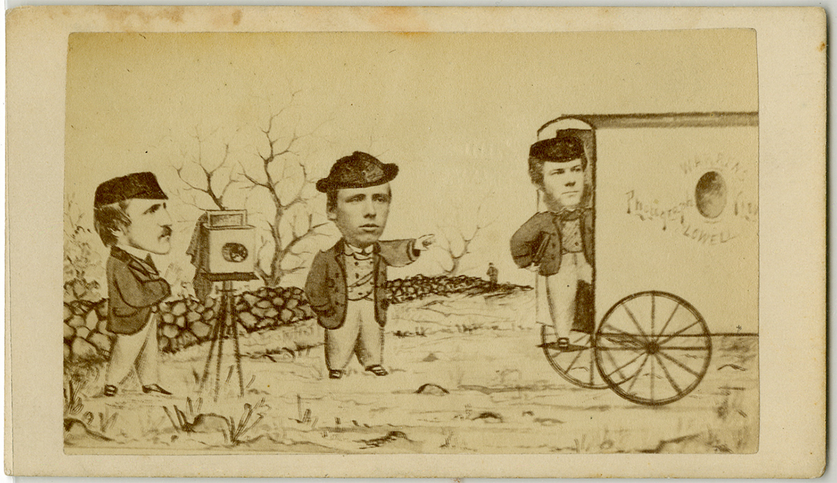 Three men with sketched bodies and photo faces stand with a camera, by a stone wall, near a wagon