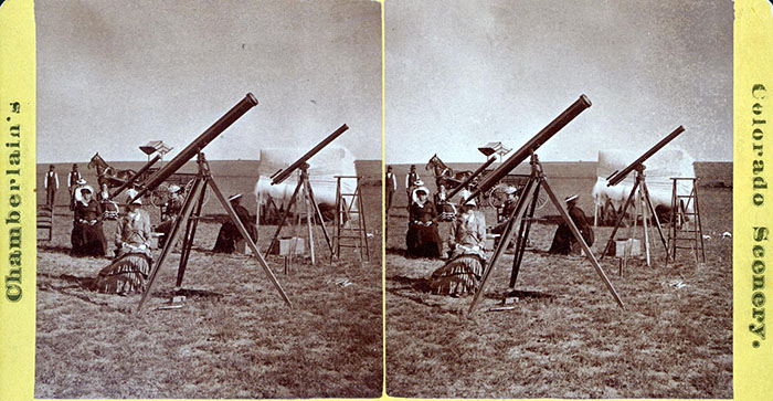 A stereoscope card (two identical photographs side by side) of women sitting by telescopes, ready to study the eclipse.
