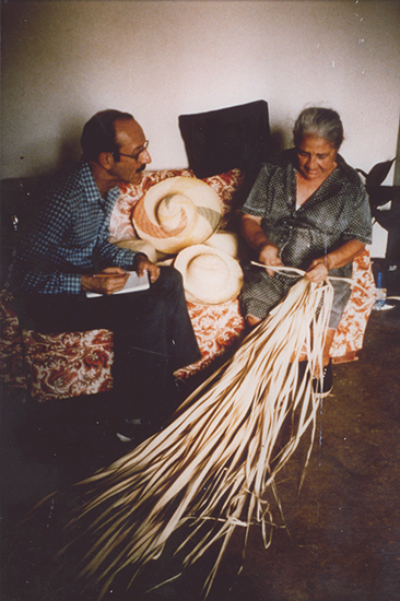 A man and woman sit on a couch. The man holds a notebook and watches as the woman manipulates long fibers to create a hat.