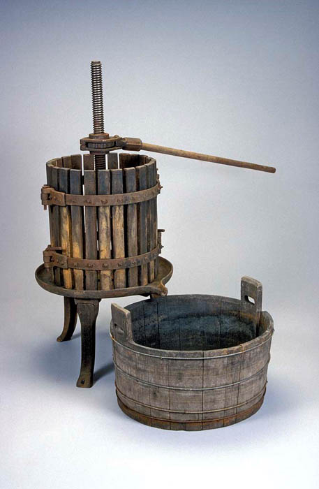 A wooden bucket, and wooden contraption standing on three legs with some sort of crank in the center.