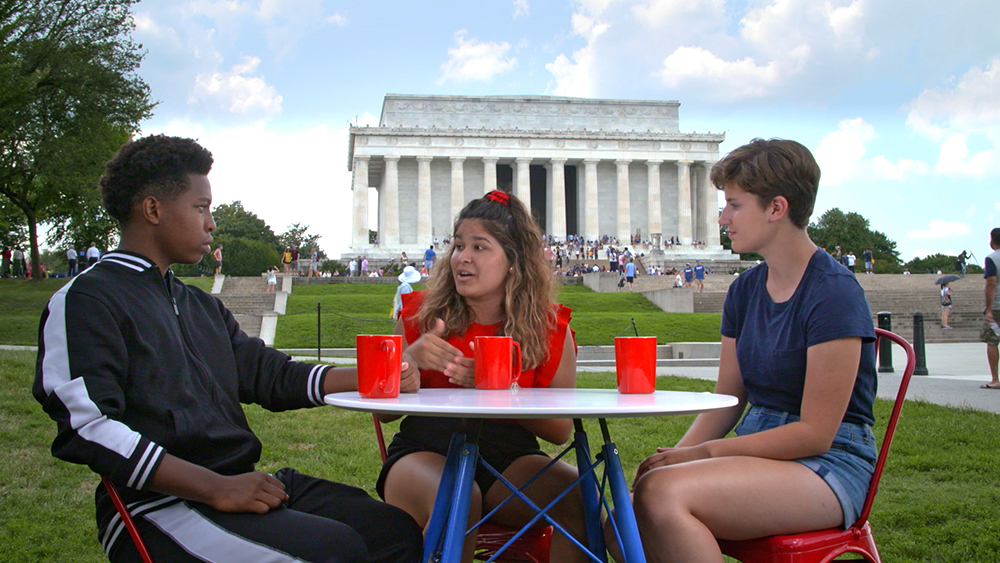 Three young people sit at a table with Washington, D.C. landmarks in the background