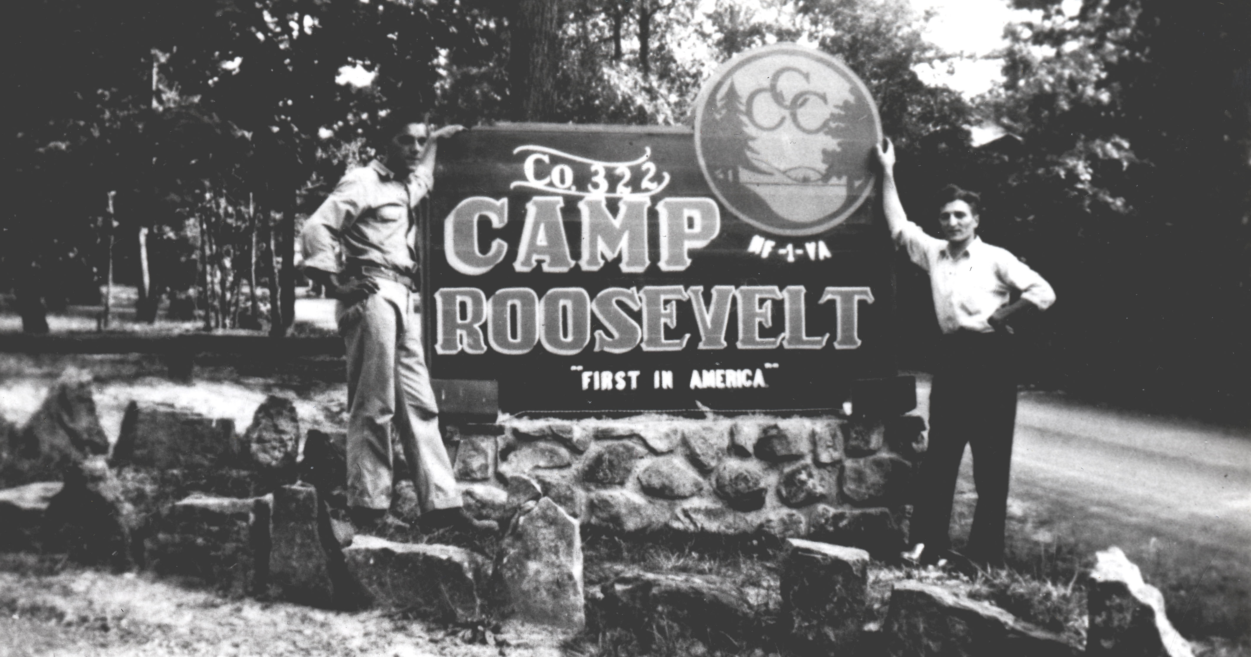 Two men pose in front of sign for Camp Roosevelt
