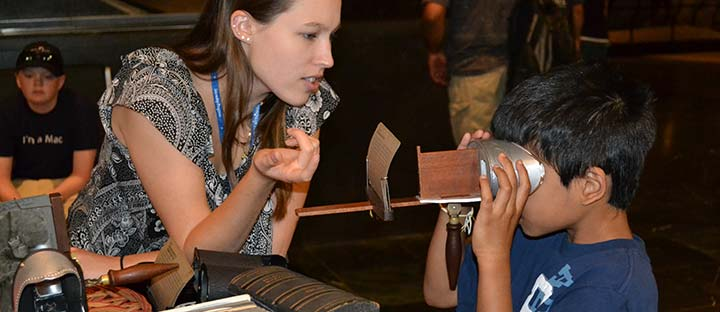 A staff volunteer shows a young visitor a stereoscope