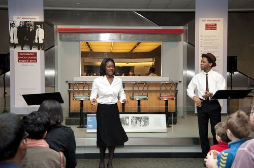 Lulu Fall and Xavier Carnegie perform Sing for Freedom in front of the Greensboro Lunch Counter