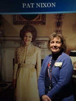 Docent Barbara Naef poses with cut-out of First Lady Pat Nixon at NMAH