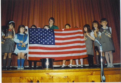 The women of my family at a Girl Scout ceremony: my sister far left, me in the blue and my mom mid-flag in green. The ceremony involved mixing red, white, and blue poker chips into a soup pot and pulling out the American flag