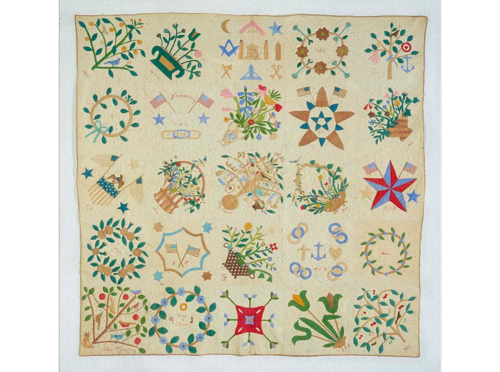 "In 1867, Susan Rogers of Brooklyn, New York, made this album quilt with 25 blocks, each with a different design. The center of the quilt is a decorated tree, under which Susan embroidered ""Merry Christmas."""