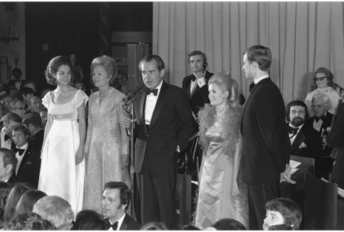 President Richard Nixon, with his wife Patricia and daughter Julie to his right and daughter Trisha and her husband Edward Finch Cox to his left, addresses the crowd at his Inaugural Ball in the Museum of History and Technology, now the National Museum of American History.