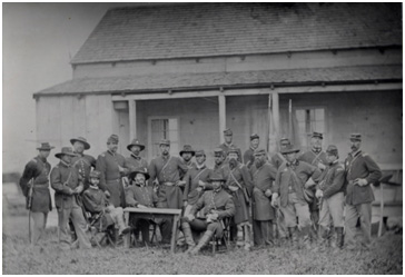 "Copy of a collodion wet plate process photograph taken of the majority of the Federal cast in front of the Leister House (General Meade's H.Q.) set building. ""Tom Chamberlain"" (C. Thomas Howell), ""General Winfield S. Hancock"" (Brian Mallon), ""Colonel Joshua Chamberlain"" (Jeff Daniels), and ""Lieutenant Pitzer"" (Bill Campbell) are around the table. Ken Burns, who had a cameo appearance as General Hancock's Aid, stands to the right of the table with his hand in his blouse. Brian James Egen stands to the right of Ken Burns. This image was used in the opening title sequence of the film."