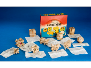 These twelve interlocking three-dimensional wooden puzzles were made in Japan, likely by the Yamanaka Kumiki Works. Each is individually wrapped in plastic and includes a sheet showing how to assemble it. A trademark on the bottom of the box includes an image of a globe surrounded by the letters T T N Y. According a 1978 application to the US Patent and Trademark Office by the Traveler Trading Company, Inc., the mark was first used in commerce in 1950.