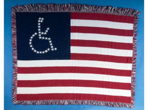 This commercially marketed lap blanket was altered by hand to include the universal access symbol made up of stitched stars. It was sewn by disability-rights advocates affiliated with ADAPT, which stands for the American Disabled for Attendant Programs Today. ADAPT was founded in 1983 in Denver.